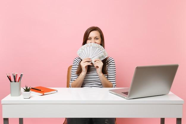 Mulher feliz cobrindo a boca com um pacote de muitos dólares, dinheiro vivo, trabalhando no escritório, na mesa branca, com o laptop do pc