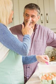 Mulher feliz colocando farinha no nariz dos maridos