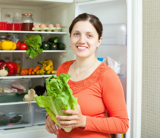 Mulher feliz colocando vegetais na geladeira