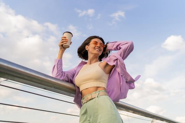 Mulher feliz com a figura perfeita em uma elegante camisa roxa grande, desfrutando de uma xícara de café enquanto caminha na ponte moderna