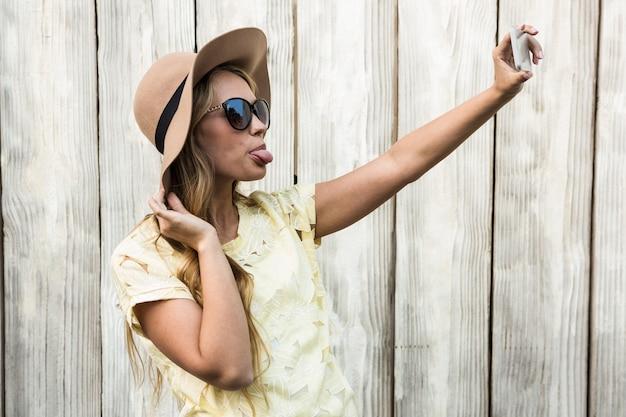 Mulher feliz com a língua estendida a tirar uma selfie