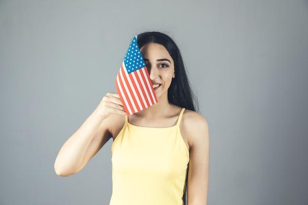 Mulher feliz com a mão na bandeira americana cinza