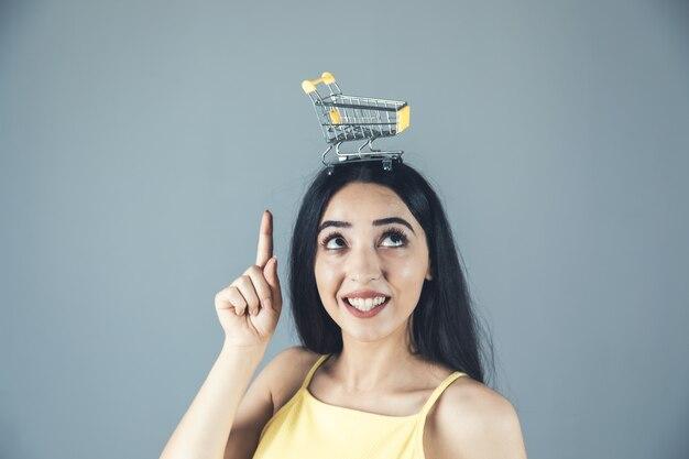 Mulher feliz com a mão na cesta de compras cinza