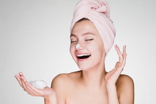 Mulher feliz com a toalha na cabeça após o banho aplicar espuma no rosto