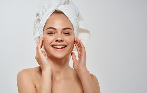 Mulher feliz com a toalha nos ombros nus de cosmetologia de pele limpa cabeça.