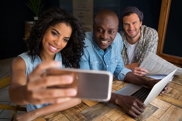 Mulher feliz com amigos tirando selfie em uma mesa de madeira em uma cafeteria