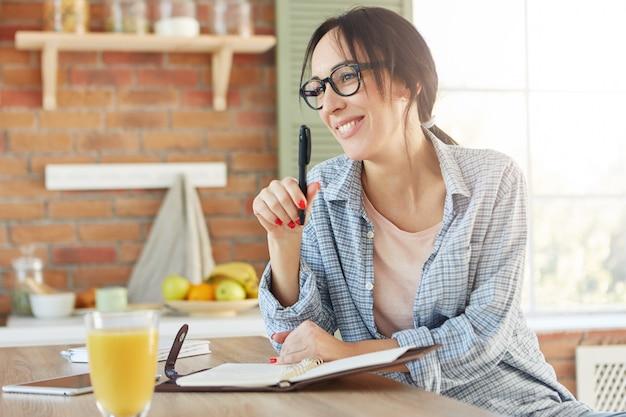 Mulher feliz com aparência atraente, vai organizar festa, faz lista de amigos convidados, senta na cozinha,