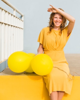 Mulher feliz com balões amarelos