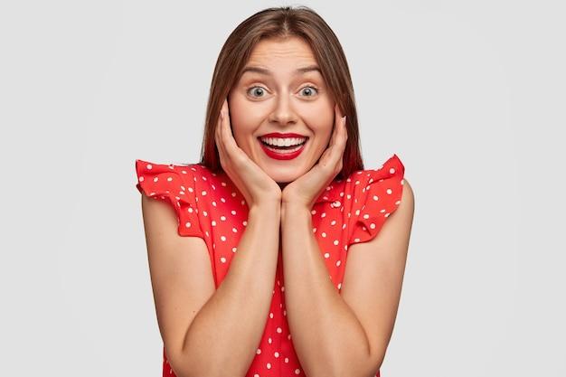 Mulher feliz com batom vermelho posando contra a parede branca