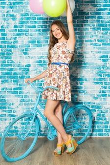 Mulher feliz com bicicleta em pé contra a parede de tijolos