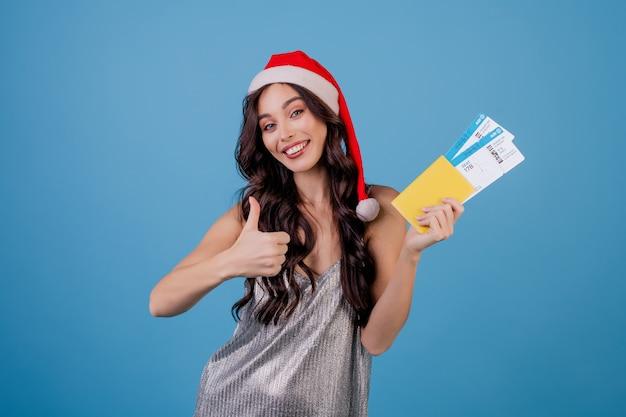 Mulher feliz com bilhetes de avião e passaporte com chapéu de natal isolado sobre o azul