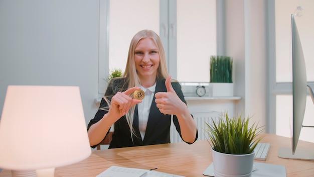 Mulher feliz com bitcoin aparecendo os polegares. mulher loira alegre sorridente em um terno de escritório sentada no local de trabalho com o computador e mostrando o bitcoin na mão, fazendo um gesto de polegar para cima e olhando para a câmera