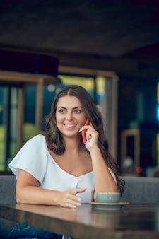 Mulher feliz com blusa branca com smartphone perto da orelha, sentada à mesa no café de verão de ótimo humor