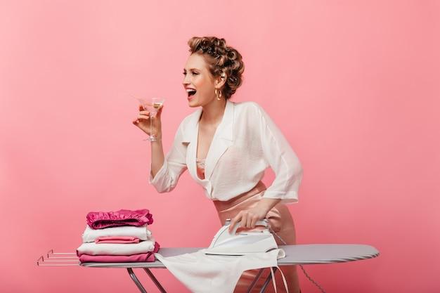 Mulher feliz com blusa branca e saia rosa segurando um copo de martini e ferro