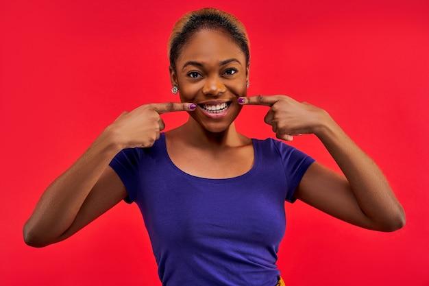 Mulher feliz com brincos e uma camiseta aponta pelos dedos para o sorriso e olha para a câmera