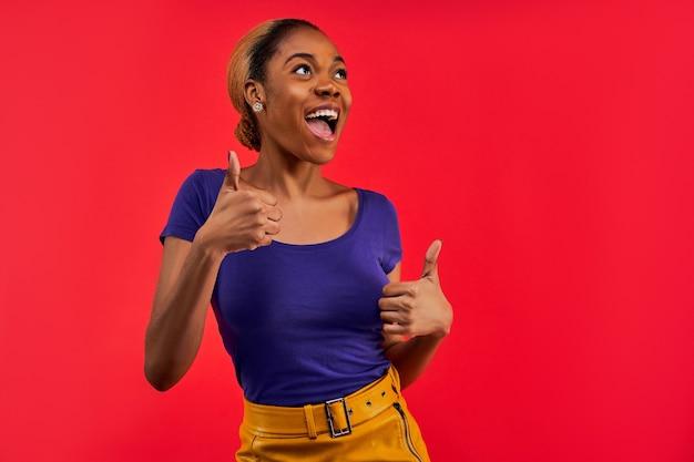 Mulher feliz com brincos em uma camiseta azul e uma saia amarela mostra um gesto semelhante