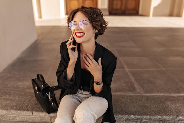 Mulher feliz com cabelo castanho em copos, sorrindo e sentado do lado de fora. jovem de jaqueta preta e calça branca fala no telefone ao ar livre.