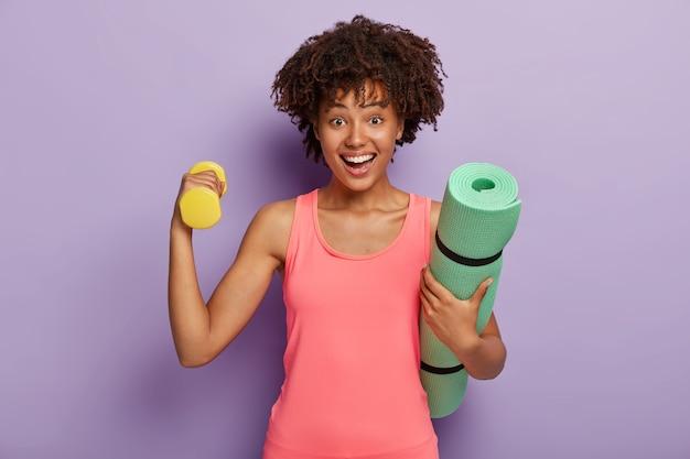 Mulher feliz com cabelo crespo, levanta halteres para treinar os músculos, usa blusa rosa e carrega tapete verde de ginástica