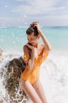 Mulher feliz com cabelo escuro, expressando emoções positivas durante a diversão no oceano. foto ao ar livre de uma linda garota bronzeada em maiô amarelo vintage.