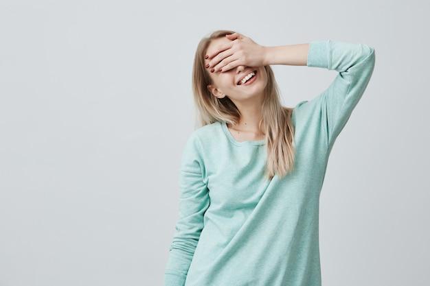Mulher feliz com cabelo loiro, fechando os olhos com a mão