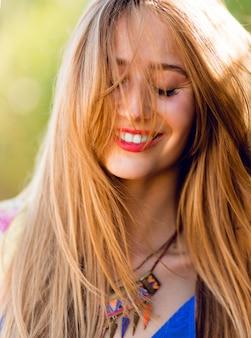 Mulher feliz com cabelo loiro ventoso e olhos fechados