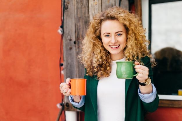 Mulher feliz com cabelos loiros encaracolados encantadores olhos azuis, segurando duas canecas de café.