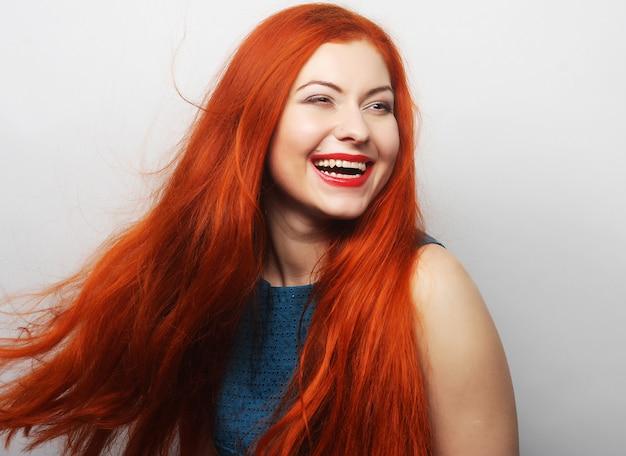 Mulher feliz com cabelos vermelhos esvoaçantes