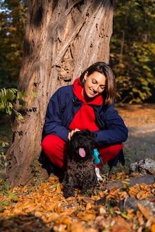 Mulher feliz com cachorro no parque com folhas outonais