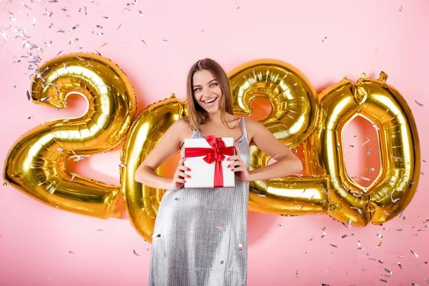 Mulher feliz com caixa de presente e confetes prata e balões de ouro ano novo 2020 isolados sobre rosa