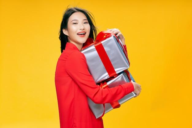 Mulher feliz com caixas de presente na exibição recortada de fundo amarelo. foto de alta qualidade