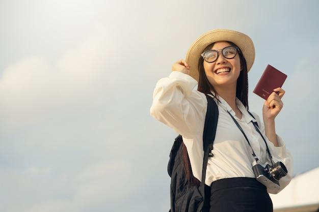 Mulher feliz com câmera e passaporte, esperando a viagem de avião.