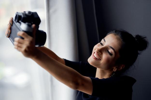 Mulher feliz com câmera fotográfica dentro de casa com janela ao fundo