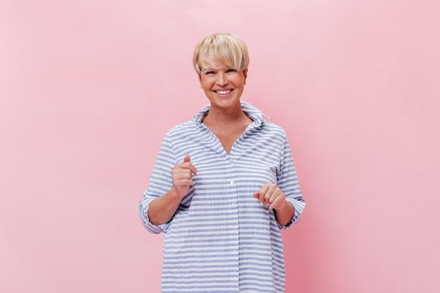 Mulher feliz com camisa olhando com um sorriso para a câmera