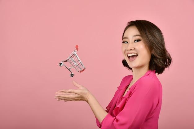 Mulher feliz com carrinho de carrinho de compras.