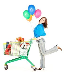 Mulher feliz com carrinho de compras e balões na parede branca