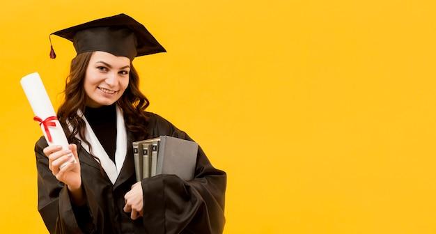 Mulher feliz com certificado e livros