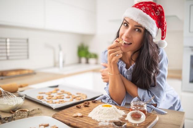 Mulher feliz com chapéu de natal, degustando seus biscoitos após um dia inteiro de cozimento para o natal. ela usa ingredientes tradicionais como farinha, mel, ovos ou canela.