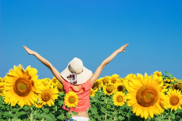 Mulher feliz com chapéu de palha no campo de girassol