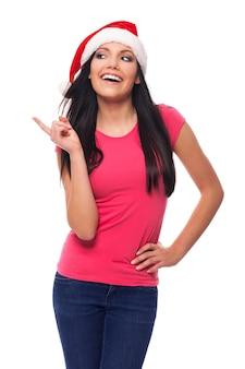 Mulher feliz com chapéu de papai noel apontando para o espaço da cópia