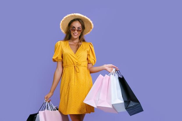 Mulher feliz com chapéu e óculos escuros faz compras enquanto sorri para a câmera preta nas grandes vendas de sexta-feira