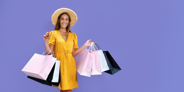 Mulher feliz com chapéu segurando óculos de sol e compras enquanto sorri para a câmera preta nas grandes vendas de sexta-feira