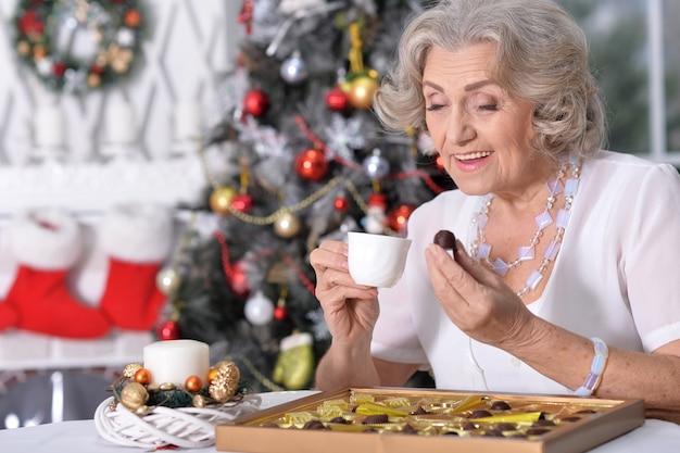 Mulher feliz com chocolates e uma xícara de chá no natal