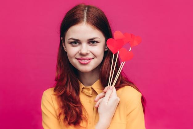 Mulher feliz com corações vermelhos no palito e camisa amarela na parede rosa