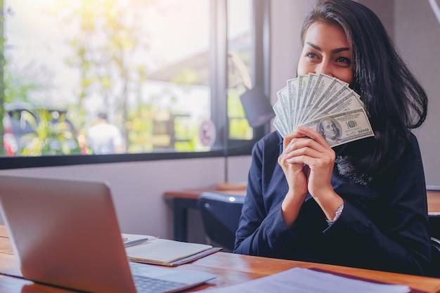Mulher feliz com dinheiro de dólares na mão dela.