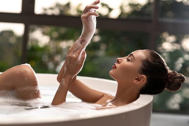 Mulher feliz com espuma branca nas mãos no banheiro luxuoso