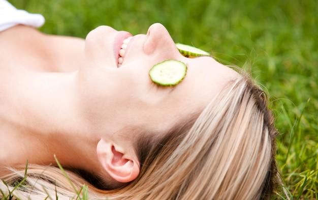 Mulher feliz com fatias de pepino no rosto