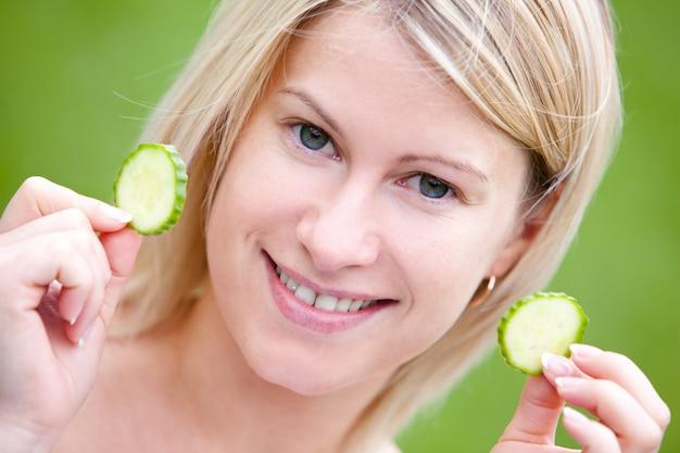 Mulher feliz com fatias de pepino
