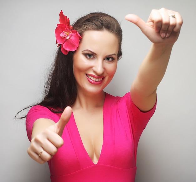 Mulher feliz com flor rosa no cabelo