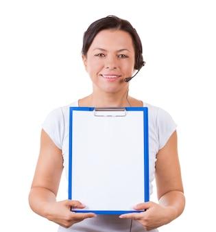 Mulher feliz com fone de ouvido trabalhando no callcenter segure a prancheta com papel em branco para seus letreiros e design em um fundo branco