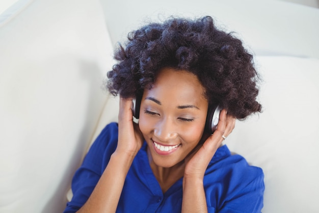Mulher feliz com fones de ouvido no sofá